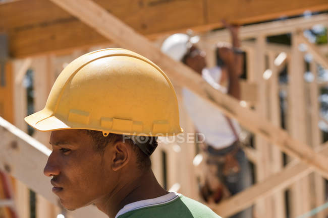 Carpenters in a framed house at a building construction site — Stock Photo