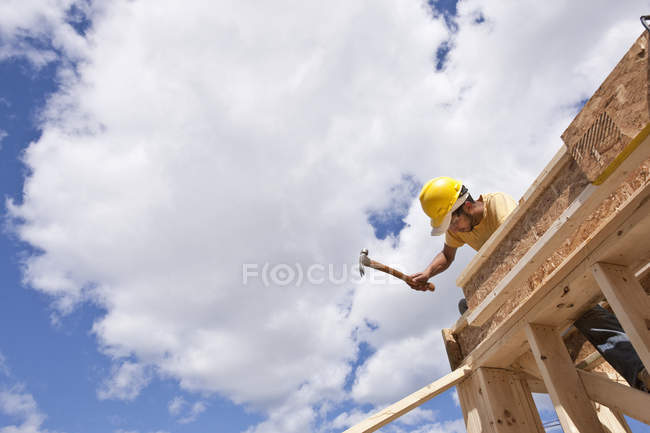 Carpenter hammering on upper floor joists at a building construction site — Stock Photo