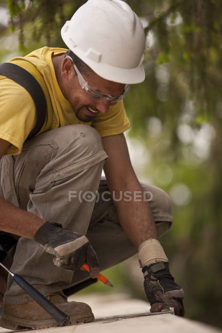 Carpenter measuring particle board and marking with a pencil at a building construction site — Stock Photo
