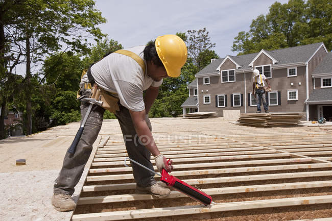 Carpenter using a caulk gun at a building construction site — Stock Photo