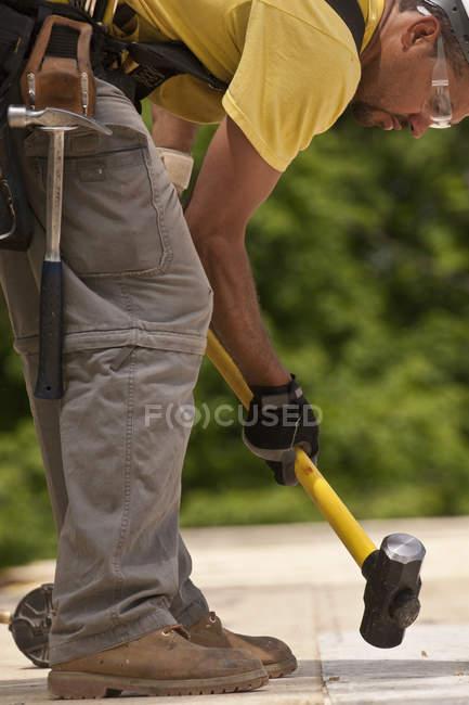 На будівельному майданчику тесляр за допомогою куваля. — стокове фото