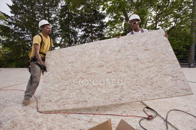 Карпентери пересувають дошку для частинок на будівельному майданчику. — стокове фото