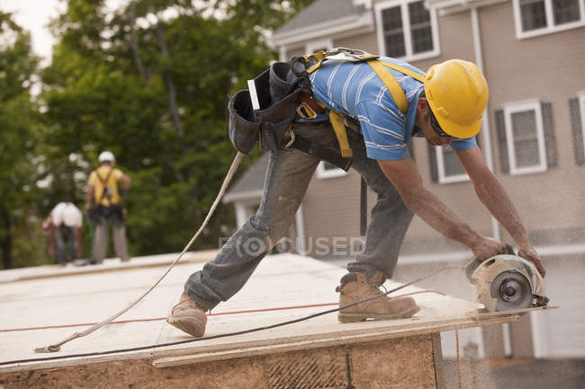 Carpenter sawing a particle board at a building construction site — Stock Photo