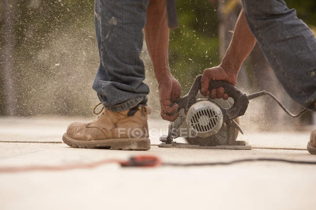 Cropped image of Carpenter sawing a board at a building construction site — Stock Photo