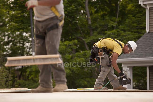На будівельному майданчику теслярі використовують мітлу та цвяховий пістолет. — стокове фото