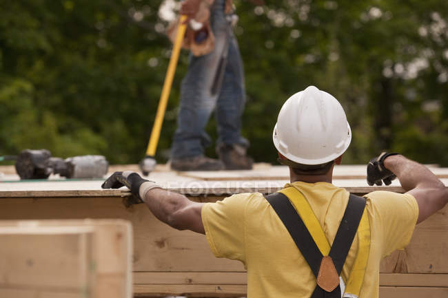 Carpenter putting a particle board in place at a building construction site — Stock Photo