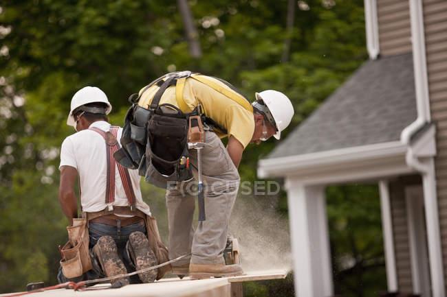 Карпентер розпилює дошку для частинок на будівельному майданчику. — стокове фото