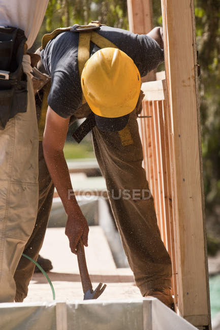 Carpenters using claw hammer at a construction site — Stock Photo