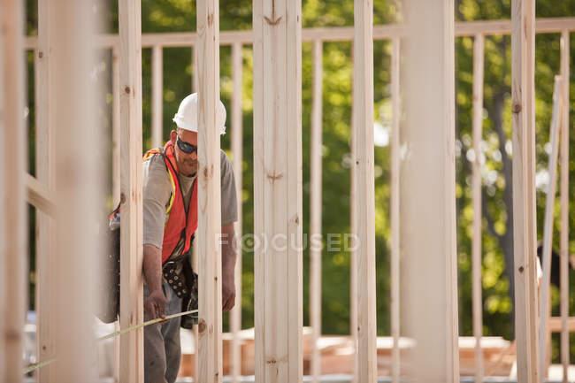 Carpenter measuring frames at a building construction site — Stock Photo