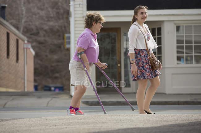 Frau mit Zerebralparese und Krücken läuft mit ihrer Schwester in der Stadt — Stockfoto