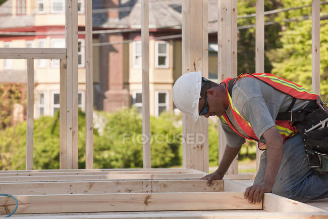 Carpenter placing wall studs in a wall frame at a building construction site — Stock Photo