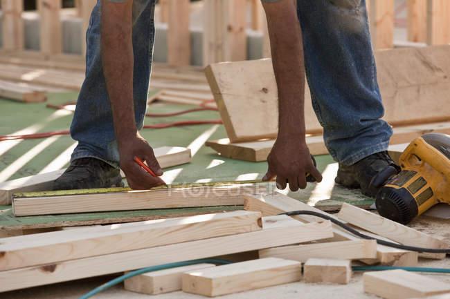 Charpentier mesurant le bois sur un chantier de construction — Photo de stock