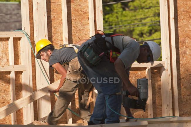 Carpenter lifting studs and using nail gun at a building construction site — Stock Photo