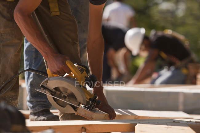 Carpenters using circular saw at a construction site — Stock Photo