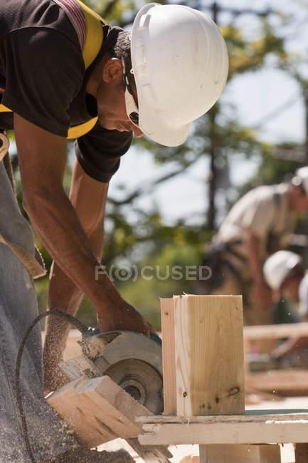 Charpentier utilisant une scie circulaire sur un chantier — Photo de stock