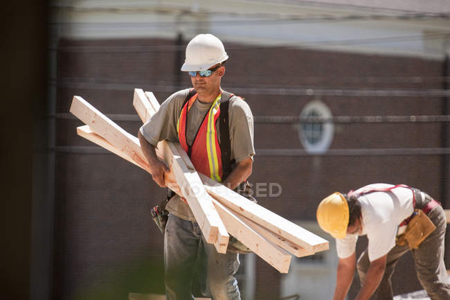 Плотники, перевозящие деревянные доски на стройплощадке — стоковое фото