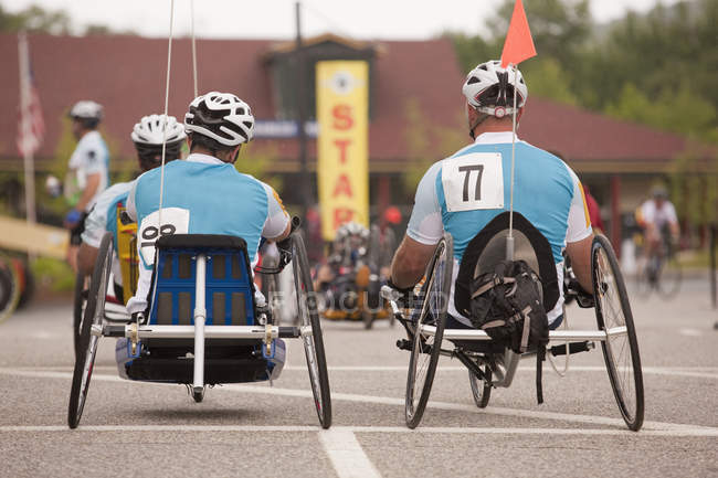 Men with spinal cord injury and leg amputee participating in a handcycle race — Stock Photo
