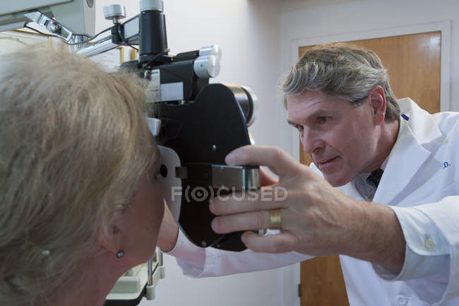 Ophthalmologist examining a woman's eyes with a phoropter — Stock Photo