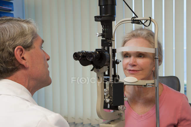 Ophthalmologist examining a woman's eyes with a slit lamp — стокове фото