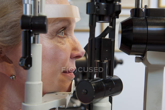 Woman getting eye exam with a slit lamp in clinic — Stock Photo