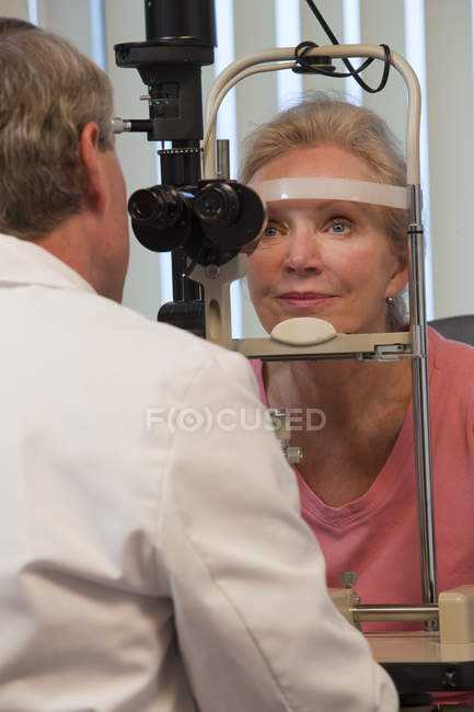 Ophthalmologist examining a woman's eyes with a slit lamp — Stock Photo