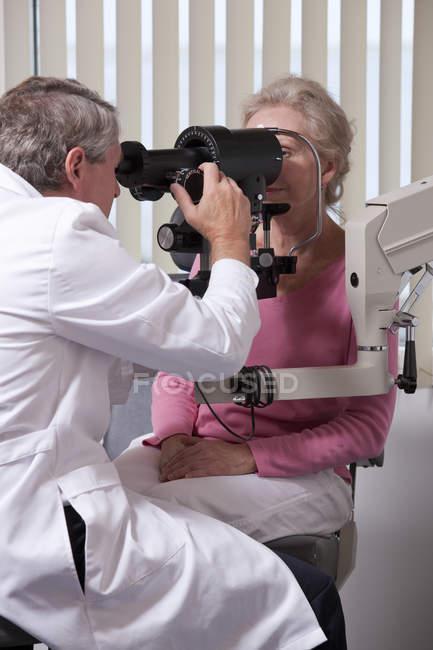 Oftalmólogo examinando los ojos de una mujer con un queratometro - foto de stock