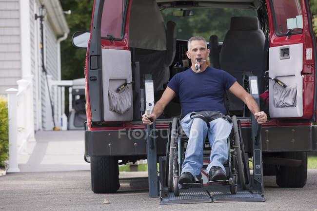 Homme avec une lésion de la moelle épinière dans un fauteuil roulant obtenir dans son van accessible — Photo de stock