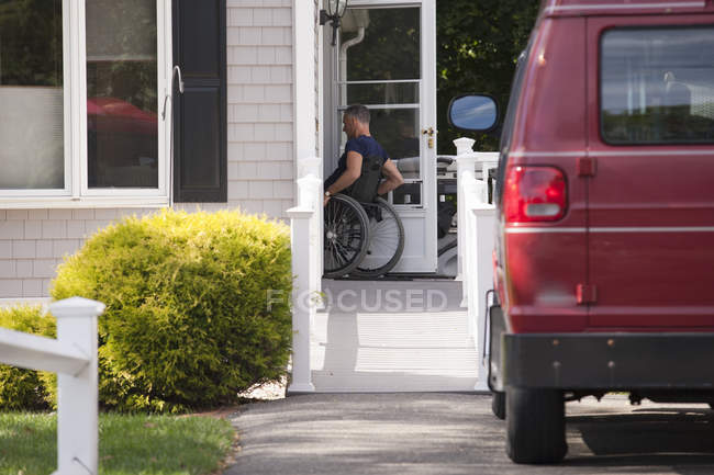 Чоловік з травмою спинного мозку на інвалідному візку їде додому. — стокове фото