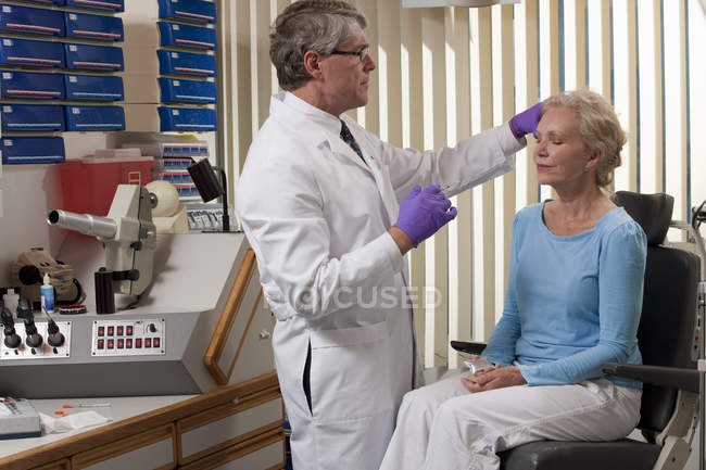 Ophthalmologist giving a Botox injection to a patient — Stock Photo
