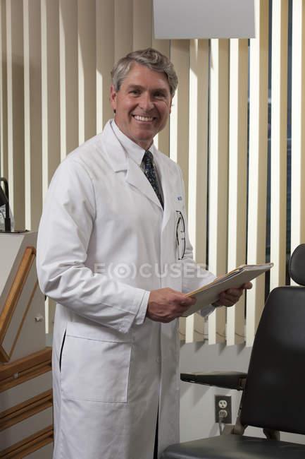 Офтальмолог изучает медицинское заключение в клинике — стоковое фото