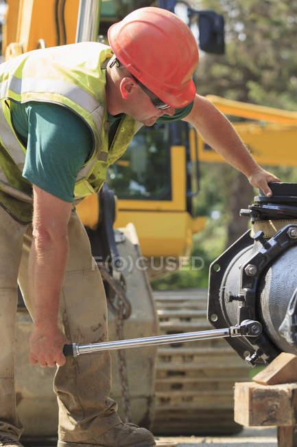 Travailleur de la construction utilisant une clé dynamométrique pour fixer la section principale de l'eau avec des boulons — Photo de stock