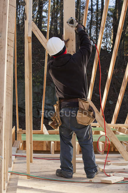 Carpenter nailing a temporary brace in place — Stock Photo