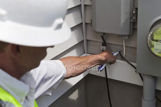 Установщик кабелей, применяющий герметик к кабелю — стоковое фото