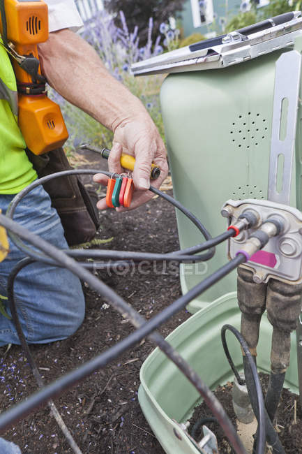 Communications worker installing tags on cable — Stock Photo