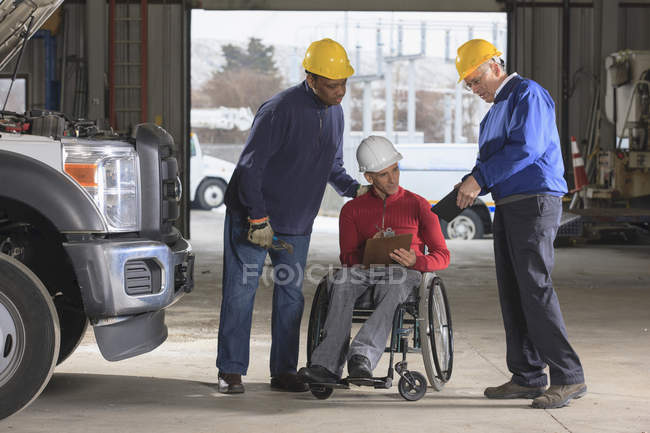 Power plant engineers one with spinal cord injury reviewing work logs in utility garage — Stock Photo