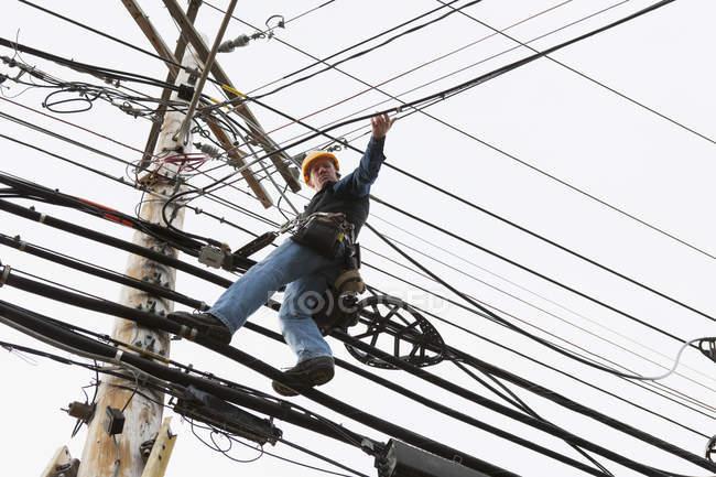 Travailleur des communications sur un poteau d'alimentation fixant des clips pour soutenir le câble — Photo de stock