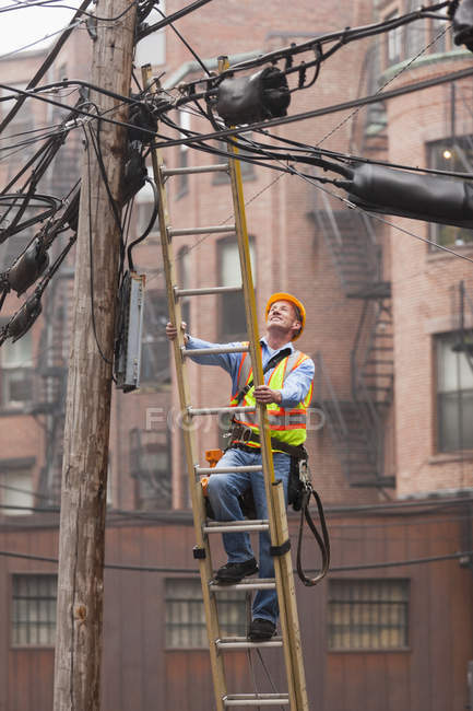 Cable lineman climbing up a ladder on city power pole — Stock Photo