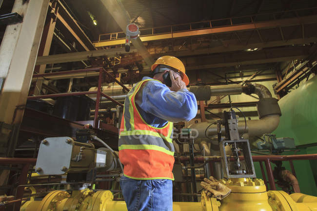 Engineer in electric power plant using his smartphone inside condenser room — Stock Photo