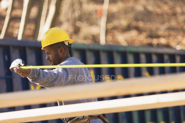 Carpenter measuring board length — Stock Photo