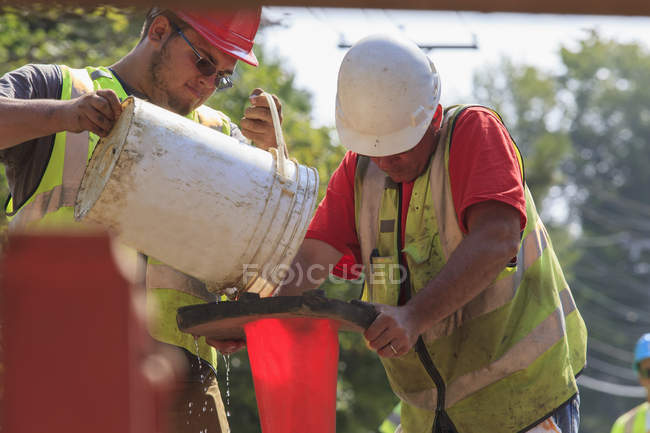 Construction workers pouring water to prime a pump — Stock Photo