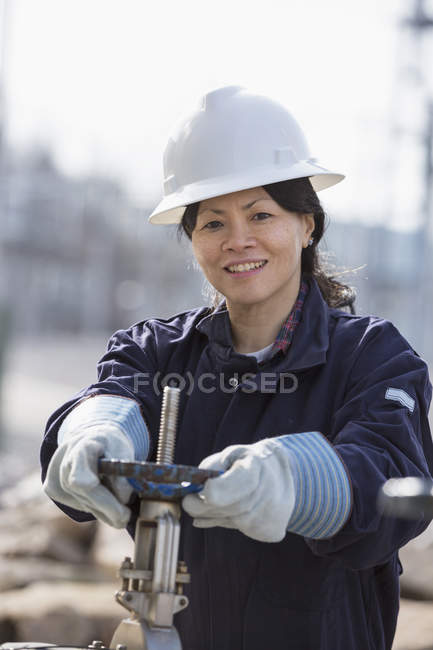 Female power engineer adjusting water valves at power plant — Stock Photo