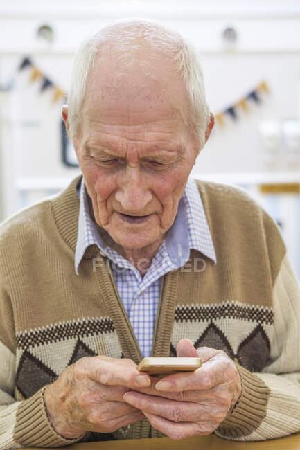 Hombre mayor a la edad de 97 con teléfono inteligente; Hartlepool, Condado de Durham, Inglaterra - foto de stock