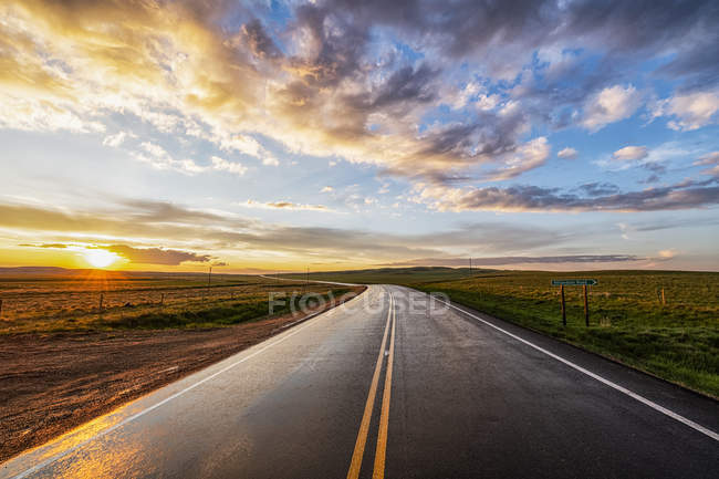 Winding country road at sunset; Val Marie, Saskatchewan, Canadá — Fotografia de Stock