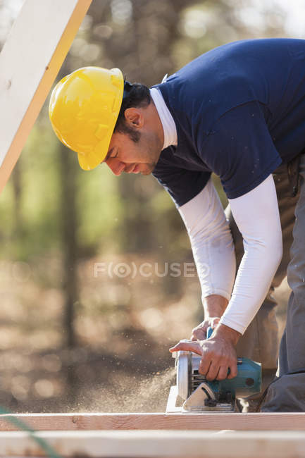Carpenter using a circular saw for house construction — Stock Photo