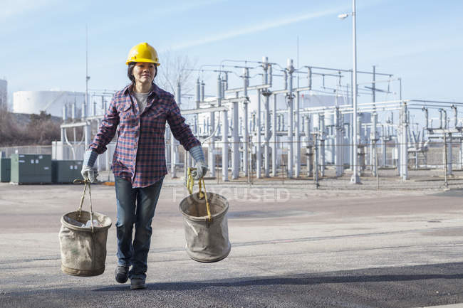 Жіночий машиніст з брезентовими відрами на електростанції. — стокове фото