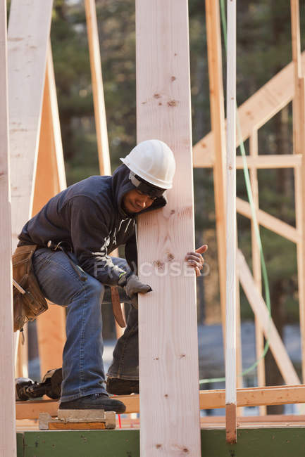 Carpenter moving roof rafter into place — Stock Photo