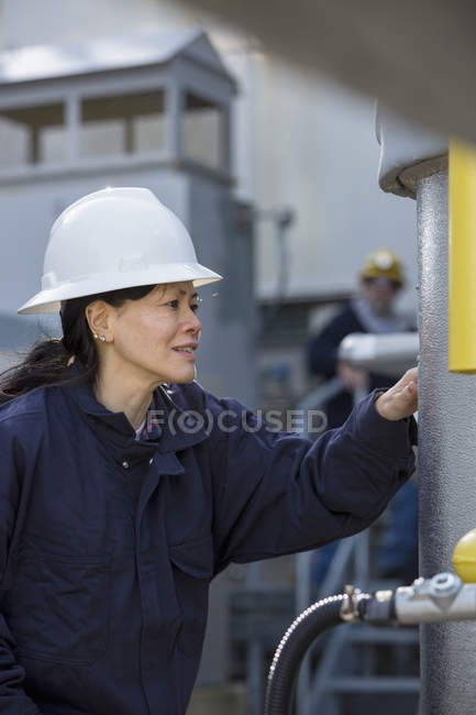 Жіночий інженер перевіряє конденсацію на електростанції. — стокове фото