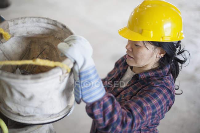Female power engineer preparing canvas bucket in service garage — Stock Photo