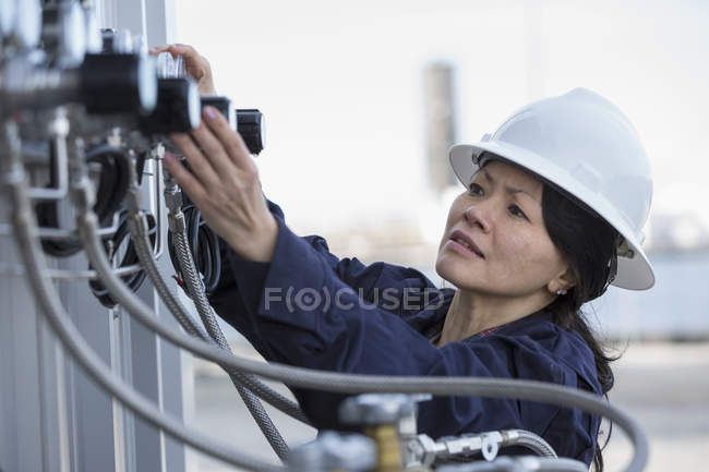 Female power engineer checking transducer at power station — Stock Photo