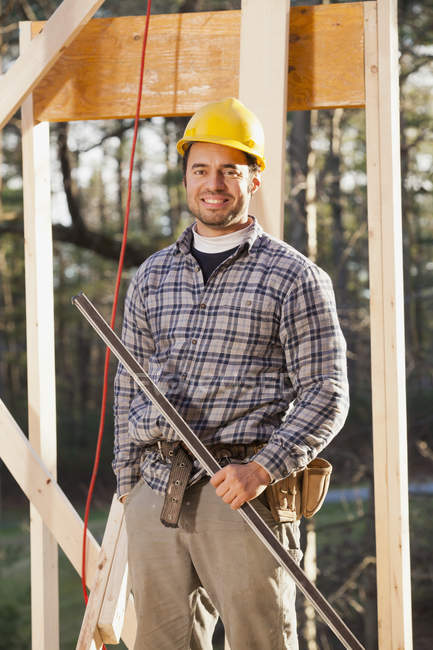 Portrait of a carpenter holding a level on house framing — Stock Photo